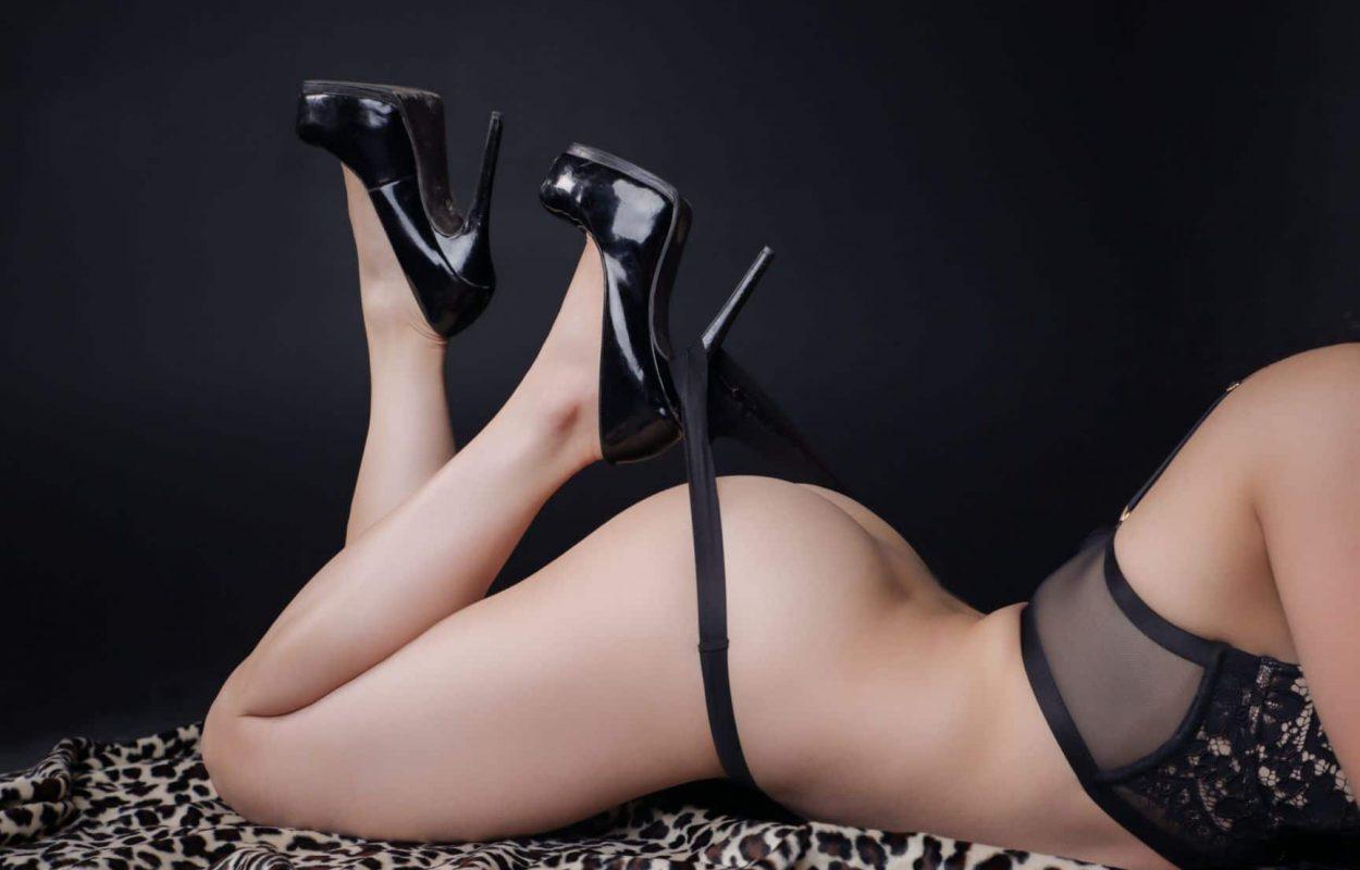 Boudoir photoshoot of woman wearing black high heals.