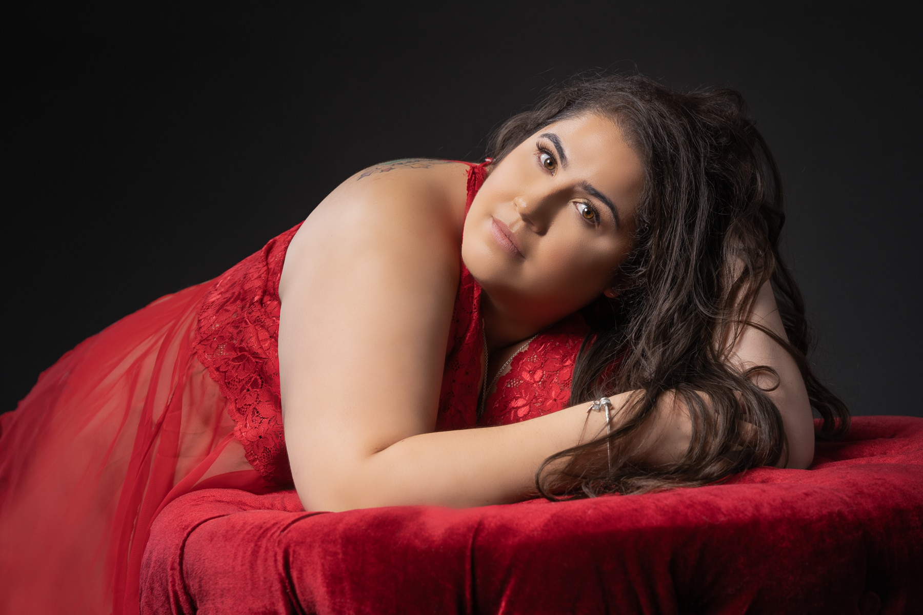 Plus size woman leaning forward in red dress.