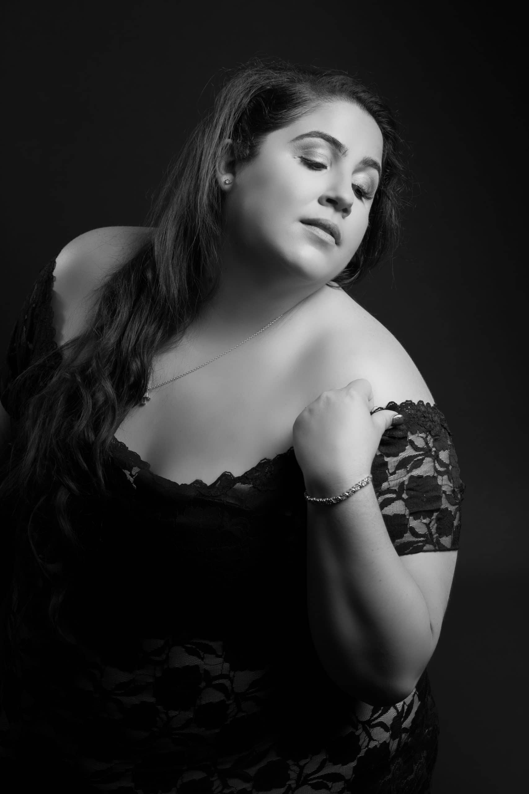 Black and white boudoir photoshoot of plus size women in black dress.
