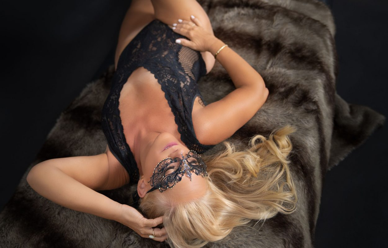 Blonde woman with black mask and outfit.