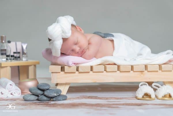 Newborn wearing white robe sleeping on wood bed.