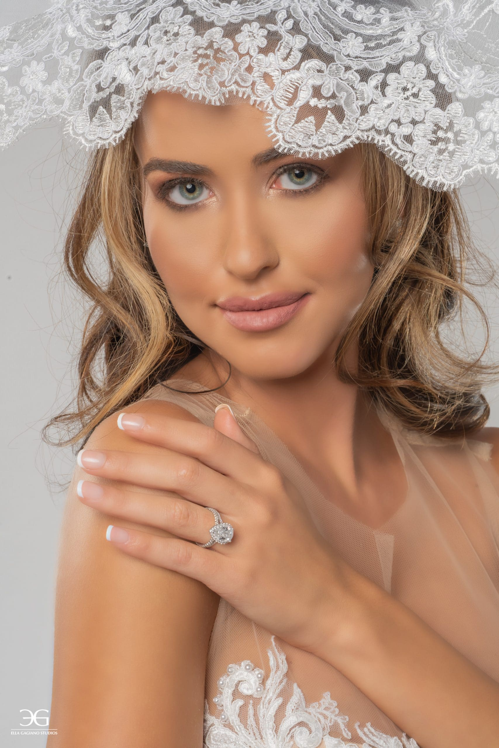 Bridal photoshoot with lacy white dress and diamond ring.